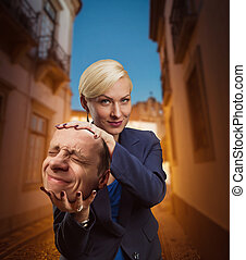 Woman with mans head in her hand - Pensive businesswoman...