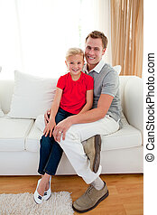 Blond little girl sitting on sofa with her father at home
