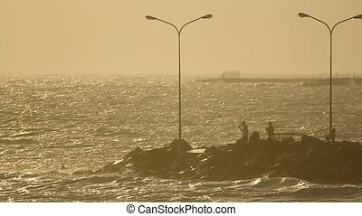 Breakwater at sunset - Breakwater and waves in the rays of...