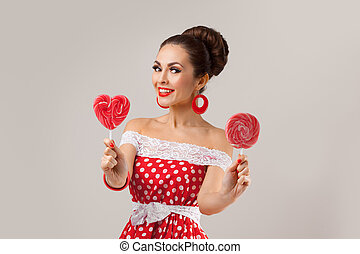 Happy Woman Holding Two Red Lollipops. Pin-up retro style.