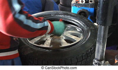 Mechanic removes car tire from disc closeup