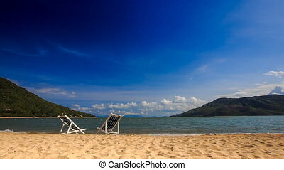 two beach chairs on sand wave surf of azure sea against blue...
