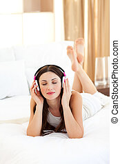 Positive woman listening music lying on bed at home
