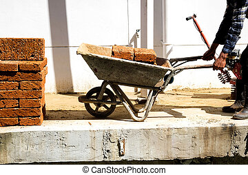 Building worker is carrying the wheelbarrow with bricks.