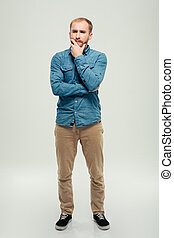 Full length portrait of a casual pensive man standing...