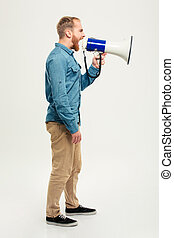 Side view portrait of a casual man screaming in megaphone...