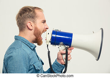 Casual man yelling into megaphone - Side view portrait of a...