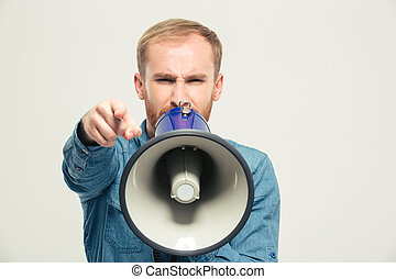 Angry man shouting in megaphone - Portrait of a young angry...