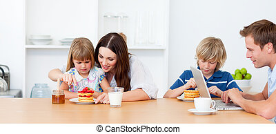Happy family eating breakfast in the kitchen at home