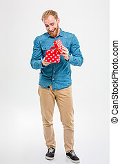 Cheerful joyful young blond bearded man opening gift - Full...