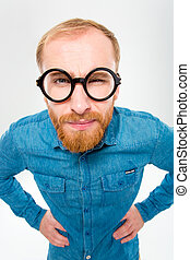 Angry amusing young man with beard in funny round glasses...
