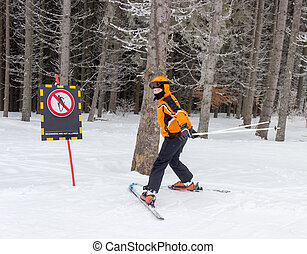 Young skier near a warning sign