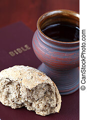 Wine and bread - Chalice with red wine and bread on a Bible....