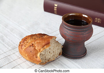 Communion - Chalice with red wine, bread and Holy Bible on a...