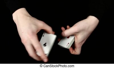 Playing cards being shuffle, on a black surface by magician...