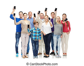 group of smiling people with smartphones - family,...