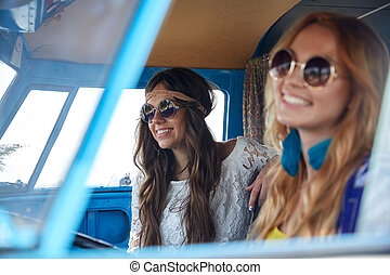 smiling young hippie women driving minivan car - summer...