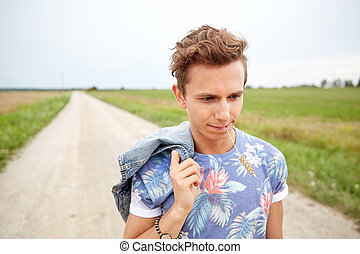 sad young hippie man walking along country road - nature,...
