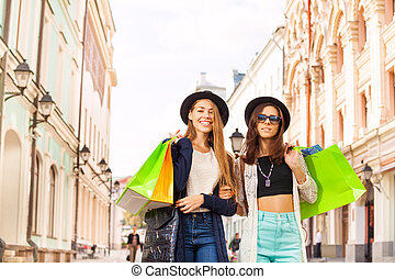 Happy young women walking with shopping bags on the street...