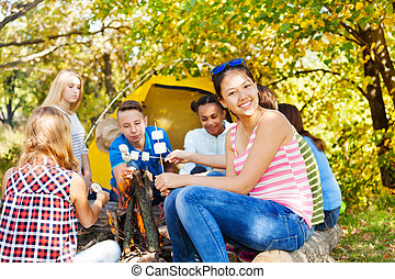 Happy teens hold marshmallow sitting on campsite near...