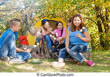 Teen friends sit on campsite with marshmallow sticks near...