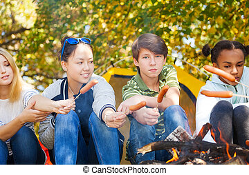 Teens sit grilling sausages on sticks, campsite - Teens sit...