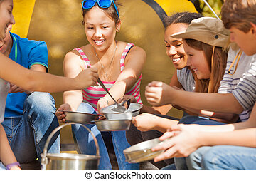 Teen pours soup in metallic plates for her friends sitting...
