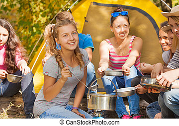 Smiling girl cooks soup in pot near yellow tent - Smiling...