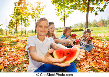 Happy children holding watermelon and eating while sitting...