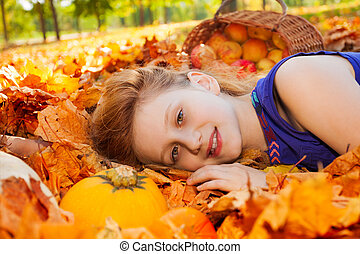 Portrait of girl on leaves with pumpkin and apples in basket...