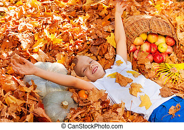 Smiling boy laying on the leaves with harvest in basket...