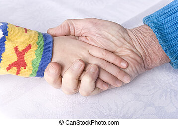 old and young generation - hand of a child and senior man on...