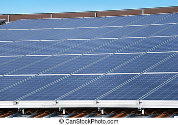 photovoltaic solar panel - solar panels on a roof with blue...
