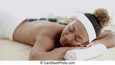 Woman Getting Hot Stones Massage At Spa - Beautiful ethnic...