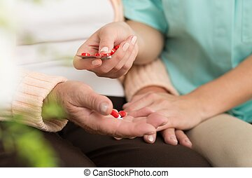 Senior patient taking pills - Close-up of senior patient...