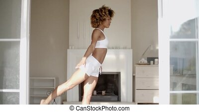Woman Stretching On Exercise Mat At Home - Fit african...