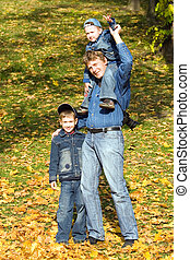 Father and sons on a bright autumn day
