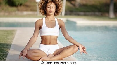 Healthy Woman Meditating Near The Pool - Young woman in...