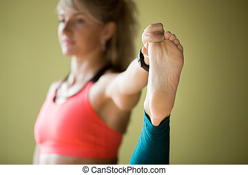 Close-up of Extended Hand-To-Big-Toe pose - Sporty beautiful...