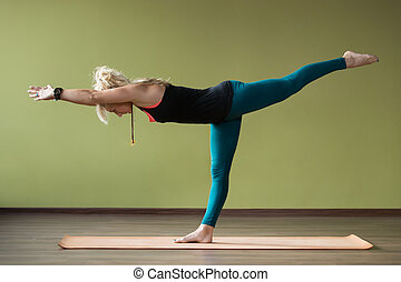 Virabhadrasana 3 Pose - Sporty beautiful blond woman in...