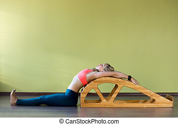Stretching exercises on yoga backbend bench - Portrait of...