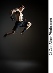 champion - Handsome muscular male athlete doing high jump...