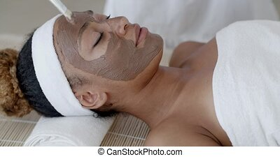 Woman With Clay Facial Mask In Spa - Portrait of girl with a...