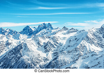 Landscape with snow in blue mountains over sky and clouds