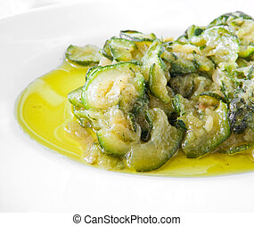 Courgettes sliced thinly and cooked with olive oil and...