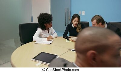 7 Business People In Office Meeting Room With Charts On TV