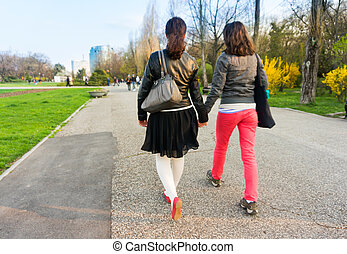 Girlfriends holding hands - Two young women are walking in...