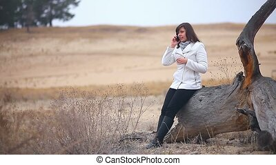 girl woman talking on the phone sitting on a dry log autumn...