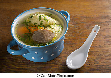 Chicken soup with dumplings in blue bowl on wooden table
