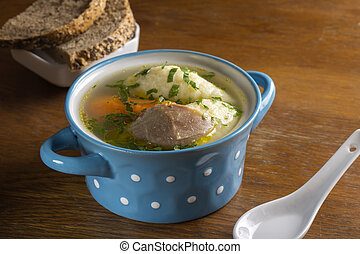 Chicken soup with dumplings and bread in blue bowl on wooden...